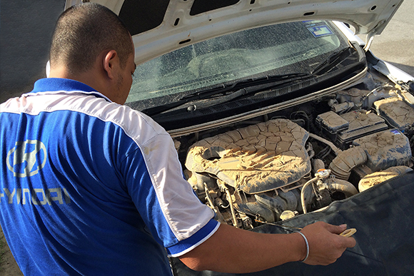 Hyundai technician inspecting a car that is damaged by the flood