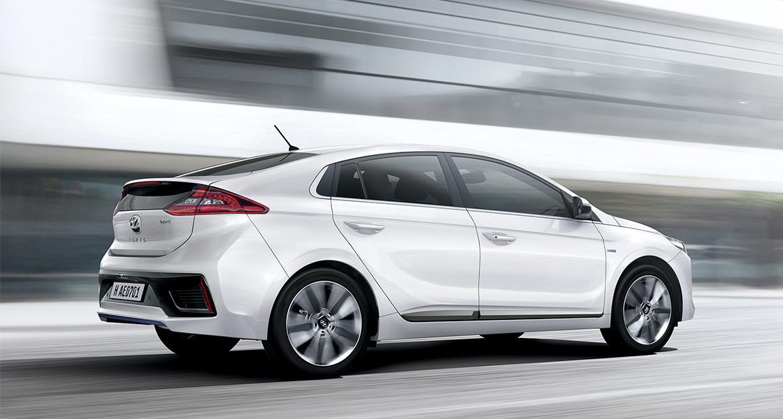 Side view of white Ioniq hybrid driving fast on the road