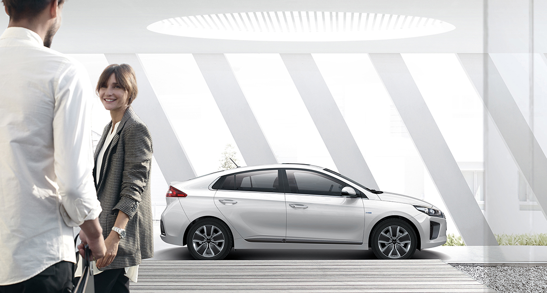 Side view of white Ioniq hybrid and a couple standing in front